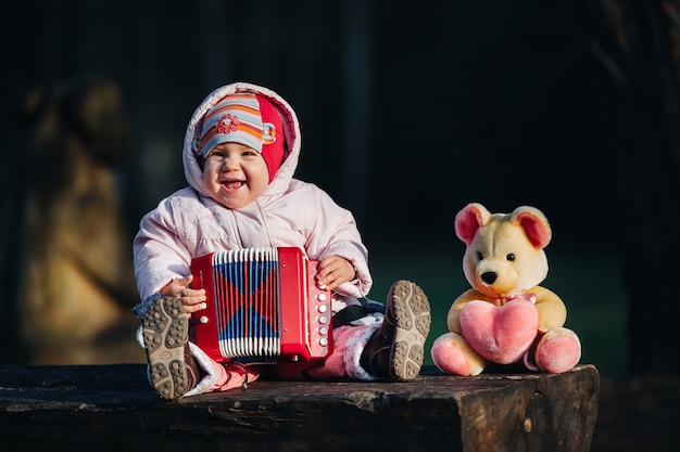 Funny cute girl, a small child in fashionable jeans plays the accordion. happy baby plays the game. cute adorable baby. beautiful expressive laugh of a smiling baby.