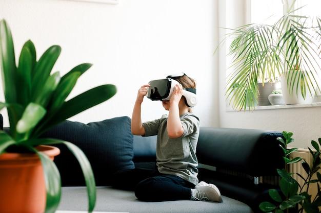 ソファに座って、仮想現実のゴーグルに表示される何かを見ている面白いかわいい女の子。現代の技術コンセプト