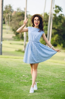 Funny cute girl wearing sky-blue dress is standing in a tropical park. girl looks surprised.