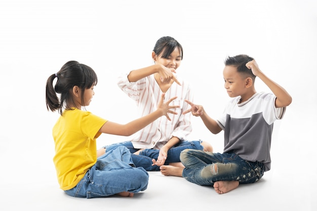 Funny and cute group of asian children playing rock paper scissors by sister being referee.