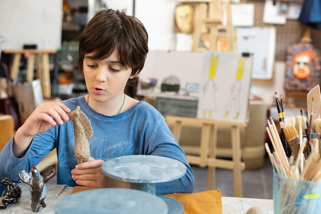 Funny cute handsome boy modeling figures out of clay