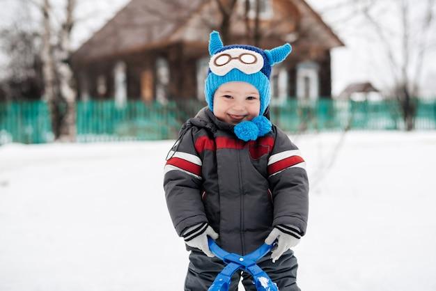 雪の外笑っている面白いかわいい幸せな男の子