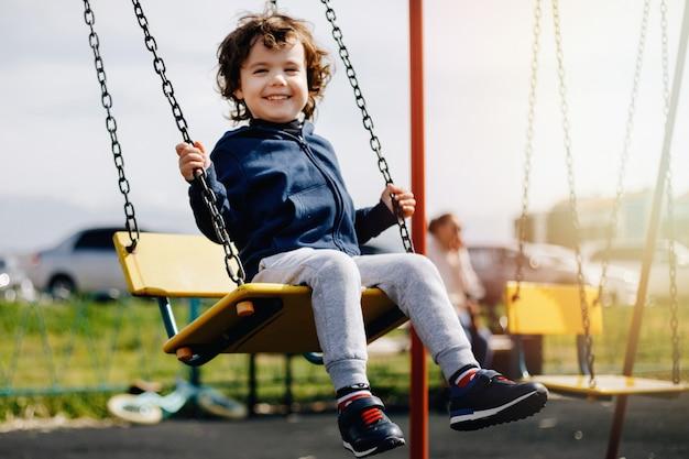 遊び場で遊んで面白いかわいい幸せな赤ちゃん。幸せ、楽しさ、喜びの感情。子供の笑顔。