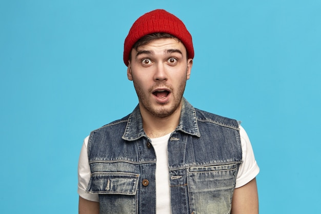 Funny cute hipster guy in stylish clothes keeping mouth wide opened expressing shock