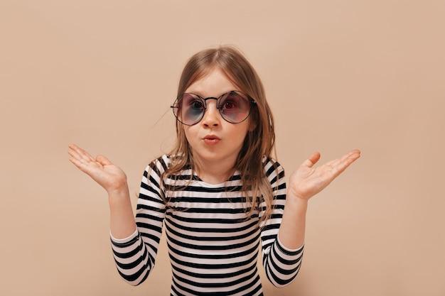 Bambina sveglia divertente 6 anni che posa alla macchina fotografica sopra fondo beige con emozioni vere sorprese