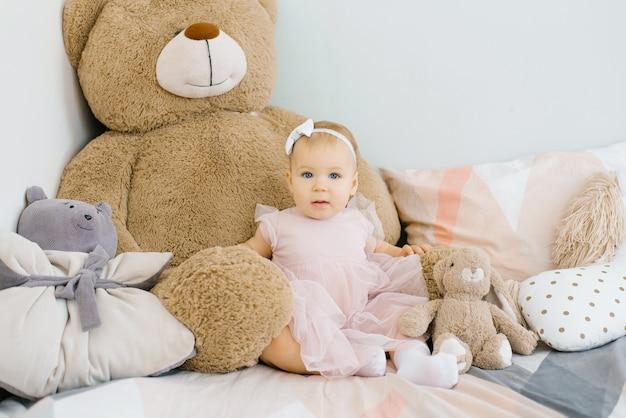 1年間おかしいかわいい女の子、朝のベッドの上に弓を頭に抱えて座っています。