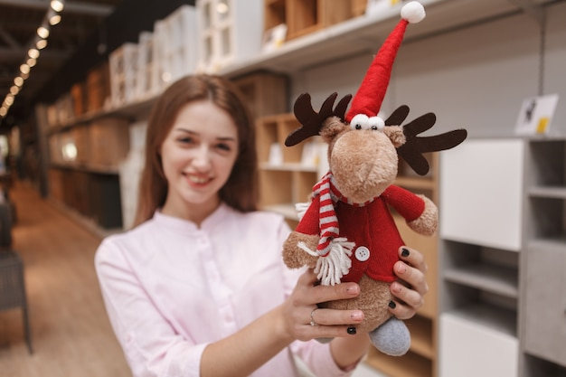 Funny cute reindeer toy in the hands of happy woman shopping for x-mas goods