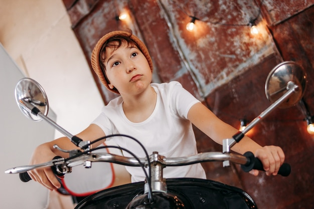 Funny cute tween boy in hat and white t-shirt on motorcycle presents himself as adult man and cool