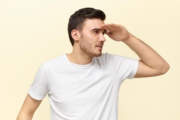 Divertente carino giovane maschio dai capelli scuri in maglietta casual che tiene il palmo sulla fronte e occhi socchiusi