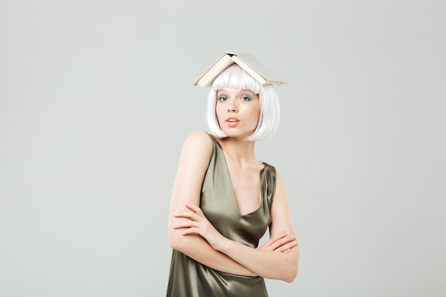 Funny cute young woman with book on her head standing with arms crossed