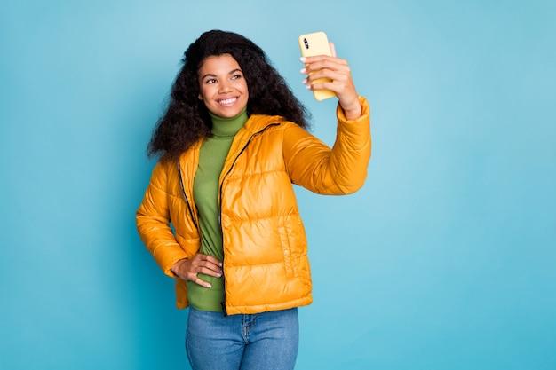 電話を保持している面白い暗い肌の巻き毛の女性selfies現代の流行のヒップスターを着用黄色の秋のオーバーコートジーンズ緑のセーター孤立した青い色の壁