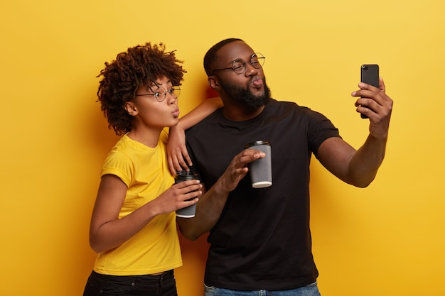 Funny dark skinned couple pouts lips at camera of cell phone, make selfie portrait, drink coffee to go from disposable cups, wear black and yellow t shirts