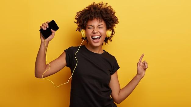 웃기는 짙은 피부색의 여성은 기분이 좋고, 리듬에 맞춰 춤을 추고, 손을 들고, 음악과 함께 노래하고, 헤드폰을 착용합니다.