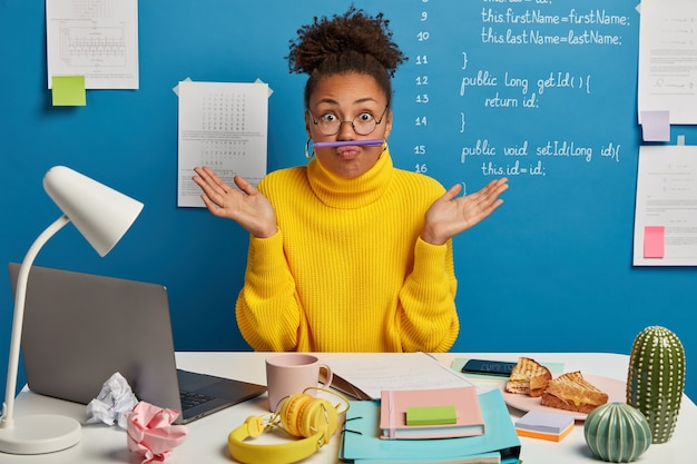 Funny dark skinned female has fun while working at desktop, keeps pen on folded lips, spreads palms, wears yellow sweater and spectacles, surrounded with laptop