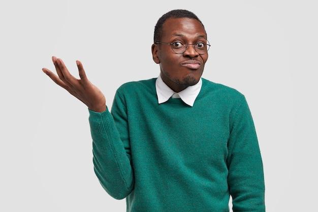 Забавный темнокожий мужчина не понимает, чего от него хочет девушка, в недоумении поднимает руку