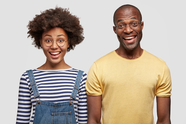 Funny dark skinned young female and male friends stand next to each other