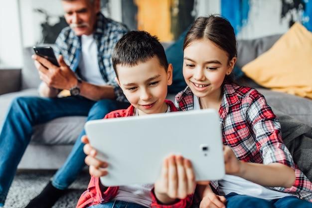 웃긴 날. 미소 형제와 자매는 할아버지와 함께 노트북으로 어머니와 이야기합니다.