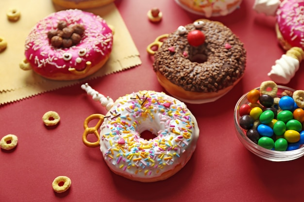 Funny decorated donuts on table