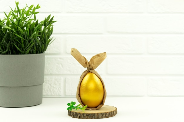 Funny decorated and painted golden egg lies on a wodden plate for easter