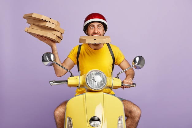 Funny deliveryman driving yellow scooter while holding pizza boxes