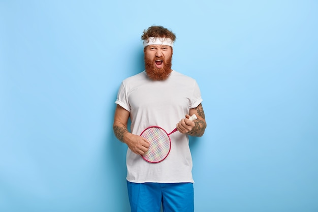 Funny determined red haired tennis player holds racket posing against the blue wall