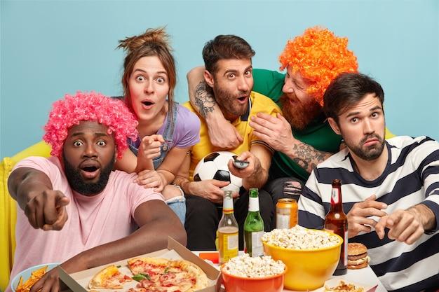 Divertenti amici diversi guardano con diverse emozioni la partita di calcio, punto alla telecamera
