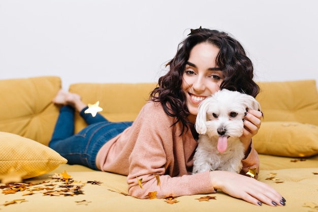 Momenti domestici divertenti di giovane donna felice che si rilassa sul divano a casa con animali domestici. divertirsi, orpelli dorati, sorridere, umore allegro, incredibili, vere emozioni positive
