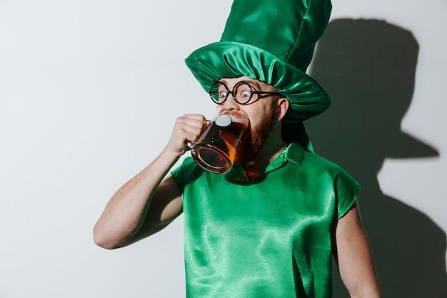 Uomo ubriaco divertente in costume di st.patriks che beve birra