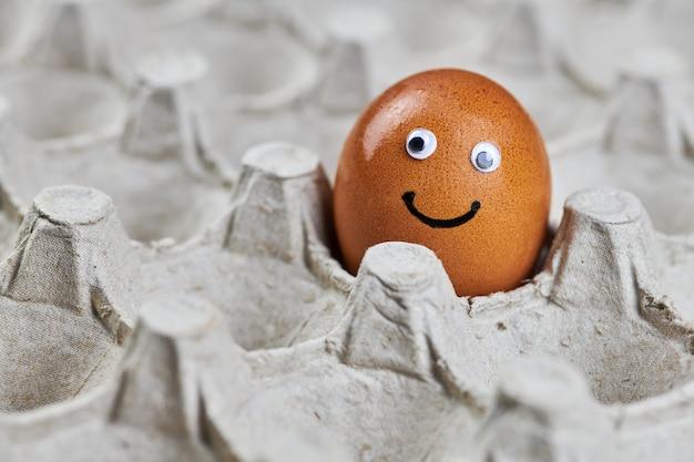 Смешное лицо пасхального куриного яйца в бумажном лотке для яиц. свежее натуральное яйцо, копия пространства. счастливое утро, концепция эмоций завтрака. качественная доставка без повреждений.