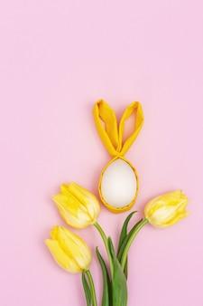 Забавная концепция пасхи. букет из желтых цветов тюльпана и деревянного пасхального яйца с тканевыми ушками в виде веселого зайчика