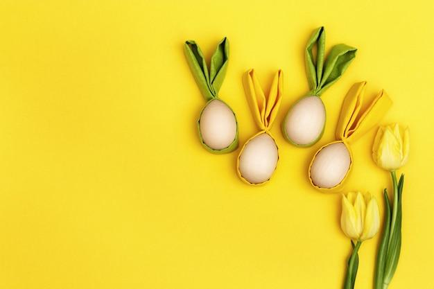 Забавная концепция пасхи. желтый тюльпан цветов и деревянное пасхальное яйцо с тканевыми ушками в виде забавного кролика.