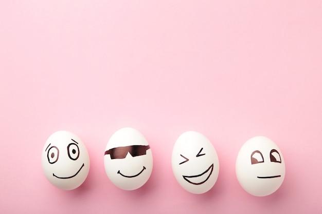 Смешные пасхальные яйца с разными эмоциями на его лице на розовом фоне.