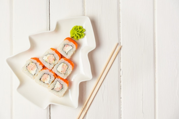 Смешная съедобная елка из суши, креативная идея для японского ресторана на белом столе. . праздник, праздник, концепция искусства еды. copyspace.