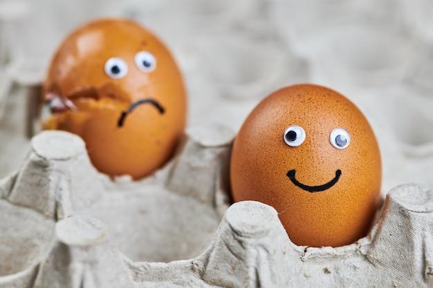 Смешное яйцо и грустное треснувшее яйцо в лотке для бумажных яиц. два пасхальных куриных яйца, свежие и натуральные. концепция доставки, копия пространства.