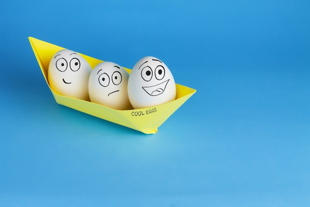 Funny eggs with drawn faces float on the ship. three white eggs in a yellow paper boat on a blue table. easter and travel concept.