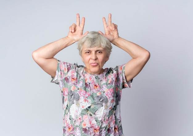 Funny elderly woman puts hands on head gesturing horns and sticks out tongue isolated on white wall