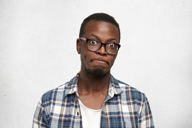 Studente maschio dalla carnagione scura dagli occhi di insetto emotivo divertente che indossa gli occhiali che trattengono il respiro