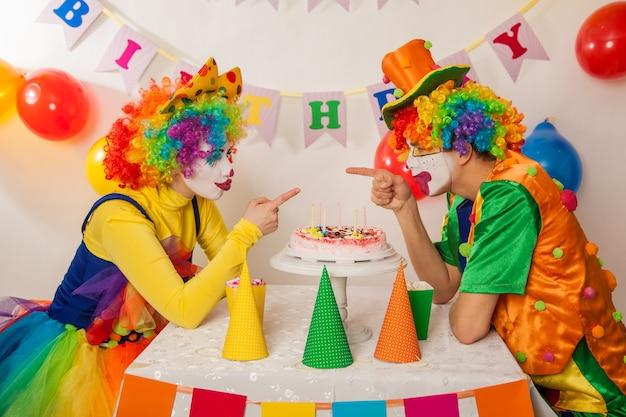 파티에서 재미있는 감정적 인 광대는 케이크를 나눌 수 없습니다