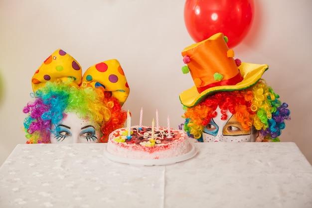 파티에서 재미있는 감정적 인 광대는 케이크를 나눌 수 없습니다 프리미엄 사진