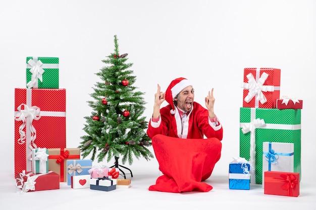 贈り物と白い背景の上の地面に座って飾られたクリスマスツリーでサンタクロースに扮した面白い感情的な興奮した若い男