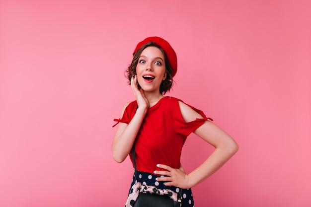 赤いブラウスのポーズで面白い感情的な女の子。スタイリッシュな服装の快適なフランス人女性。
