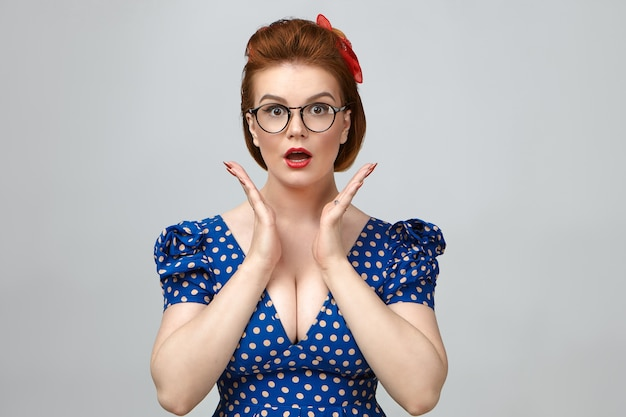 Funny emotional pin up girl wearing red lipstick, low cut dress and eyeglasses staring at camera in shock or amazement, excited with big sale prices or positive news, holding hands at her face