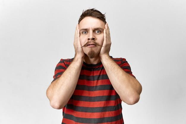 Uomo con la barba lunga emotivo divertente in camicia a righe che tengono le mani sul suo viso, perdendo la testa e la calma. ragazzo nervoso hipster con baffi gesticolando in preda al panico e preoccupazione, avendo preoccupato aspetto stressato
