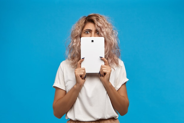 큰 도청 눈을 가진 일반 디지털 태블릿으로 얼굴을 덮고 유행 힙 스터 라운드 안경에 재미 감정적 인 젊은 여성