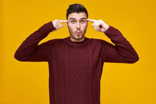 Giovane divertente emotivo in maglione marrone rossiccio accogliente con sguardo scioccato, rotolando entrambe le dita anteriori alle tempie,
