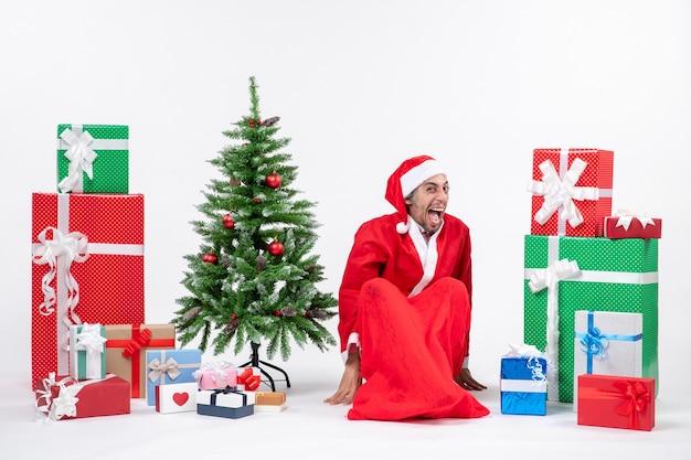 贈り物と白い背景の上の地面に座って飾られたクリスマスツリーでサンタクロースに扮した面白い感情的な若い男