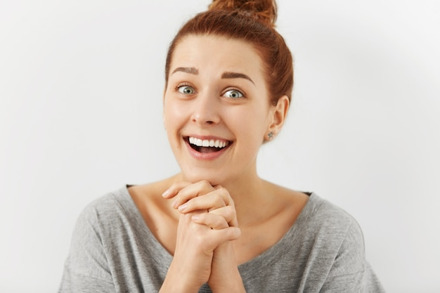Funny emotional young redhead woman with hairbun keeping hands clasped as if trying to be nice, flattering someone, asking for something. human facial expressions and emotions. body language