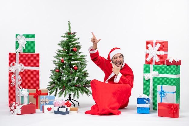 面白い感情的な興奮した若い大人は、白い背景の上を指している地面に座って贈り物と飾られたクリスマスツリーとサンタクロースに扮した