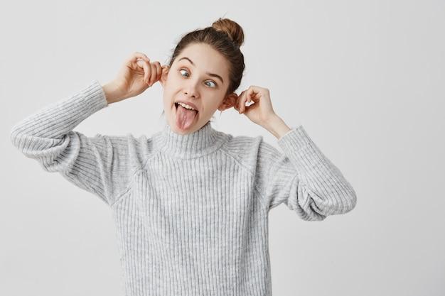 Emozioni divertenti di esilarante femmina toccando le orecchie e sporgendo la lingua. donna caucasica con capelli castani in panino tirando la faccia che fa smorfie. gioia, concetto di divertimento