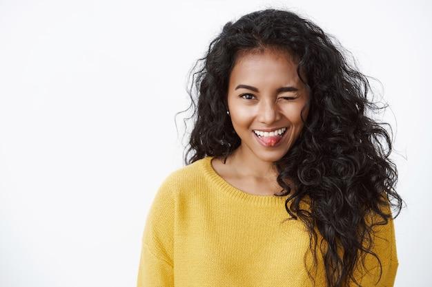Веселая, восторженная кудрявая девушка в желтом осеннем свитере глупо подмигивает и показывает язык с милым кокетливым выражением лица, стоя у белой стены, дурачится